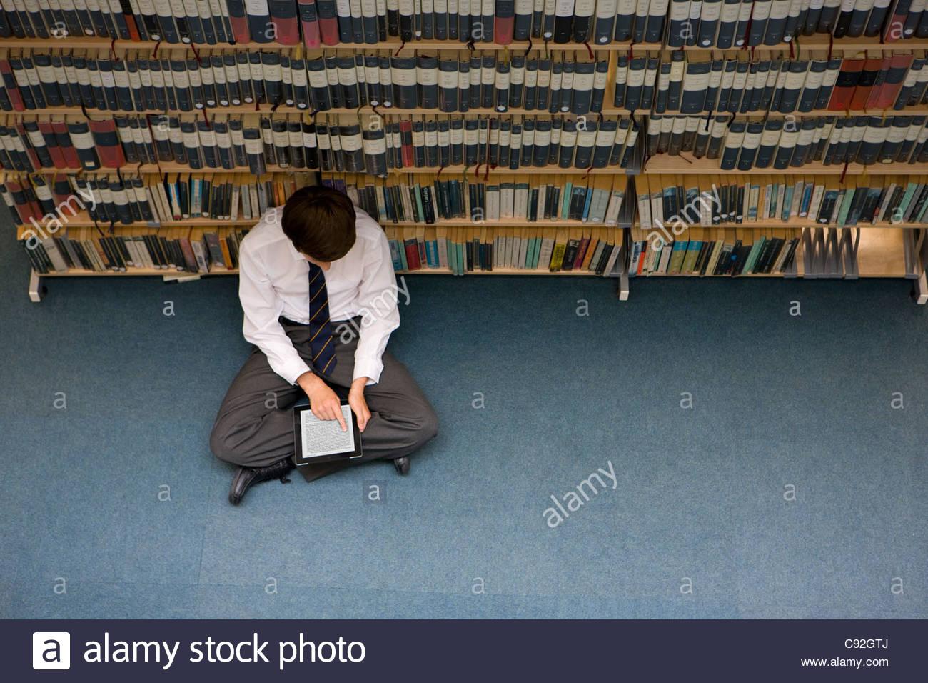 Male student lecture sur livre électronique digital tablet in library Photo Stock
