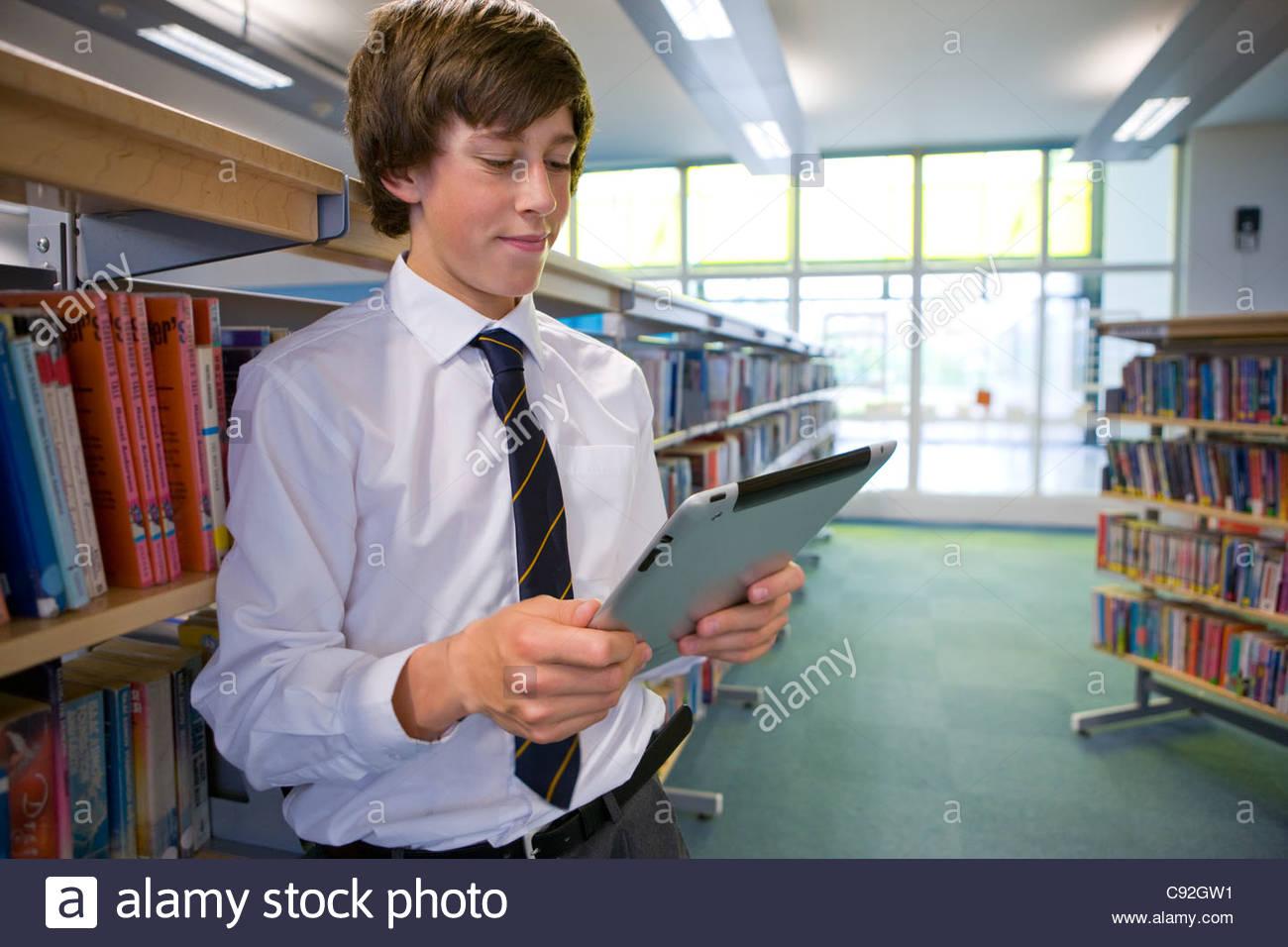 Male student lecture livre électronique sur tablette numérique dans la bibliothèque de l'école Photo Stock