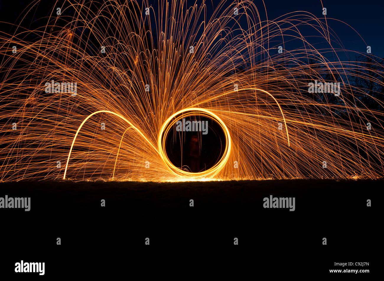 Filature de laine d'acier, créant de magnifiques traînées circulaire de lumière dorée de brûler de l'intérieur laine de fil d'un fouet attaché à fil, ou de corde. Banque D'Images