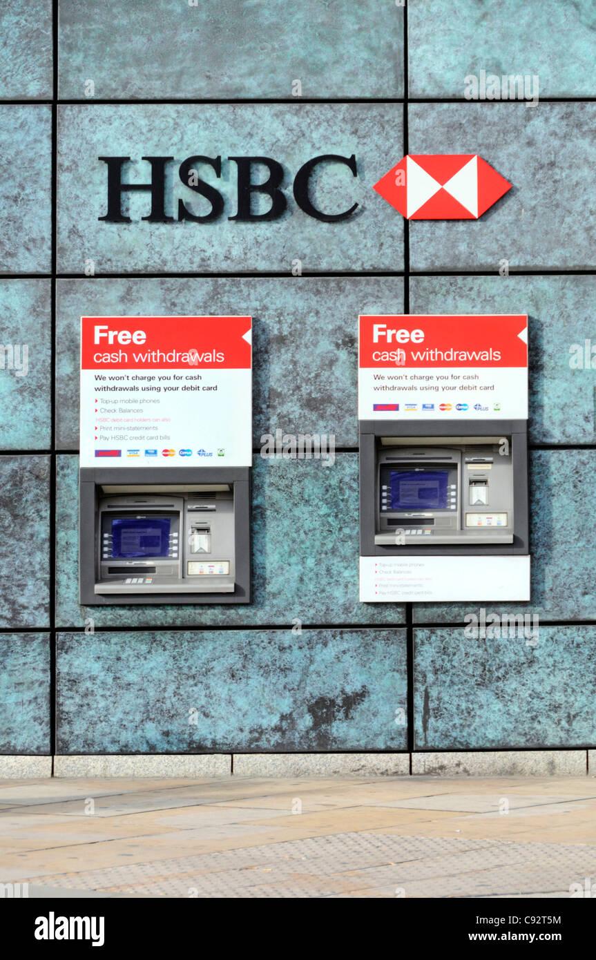 Deux distributeurs de billets ATM de la banque HSBC de retirer de l'argent dans un trou dans le mur de la banque ci-dessous logo banque signe et dans City of London England UK Banque D'Images