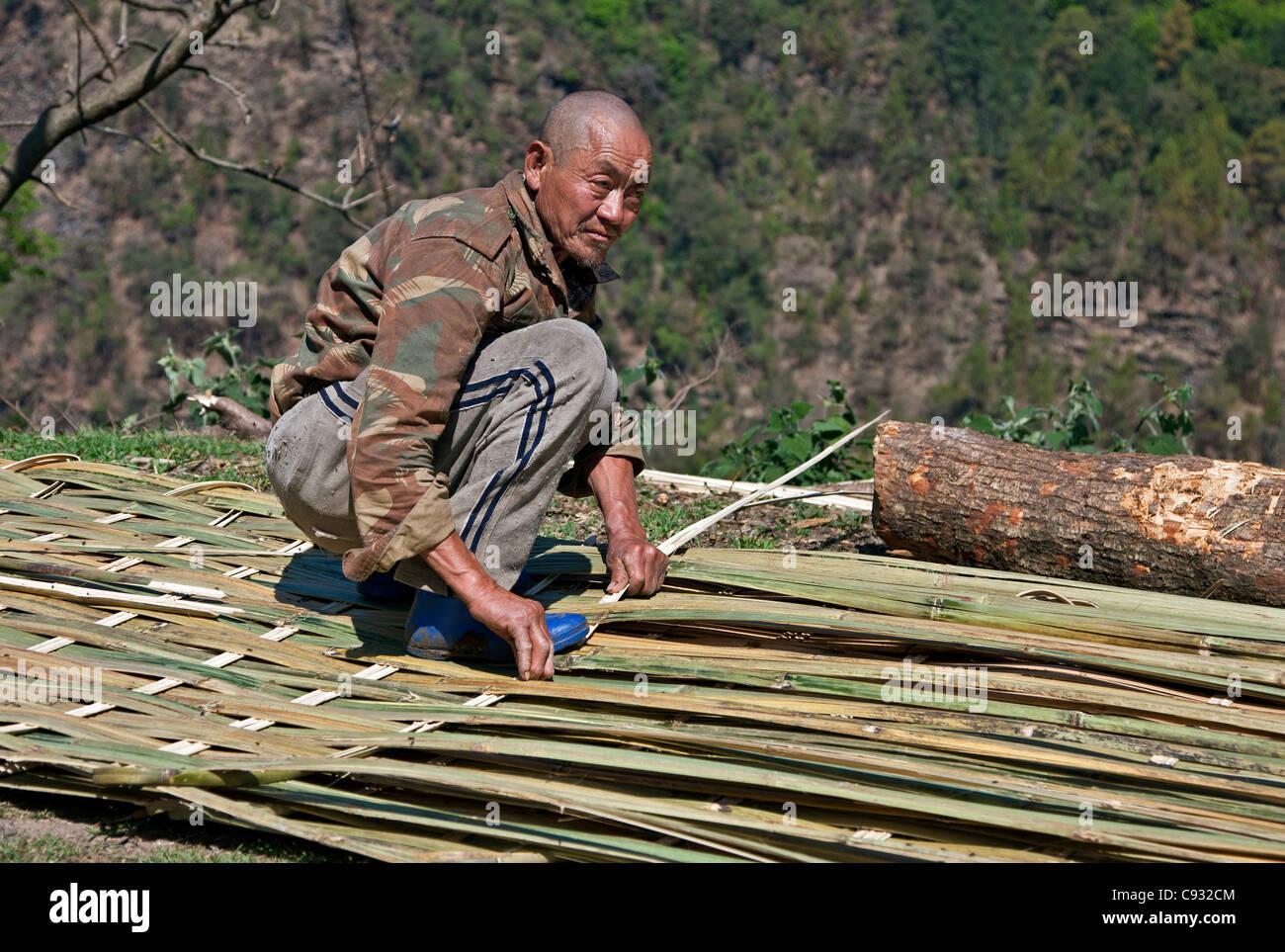 Un homme fait des grilles pour l'walling et plafonds de maisons ou pour les clôtures de bambou fendu. Photo Stock