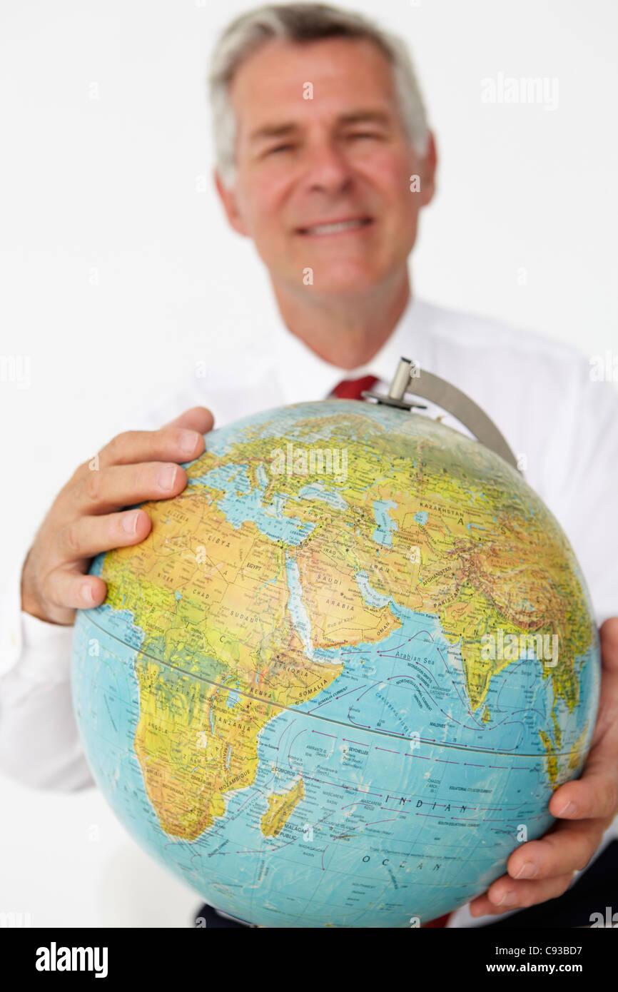 Senior businessman holding globe Banque D'Images