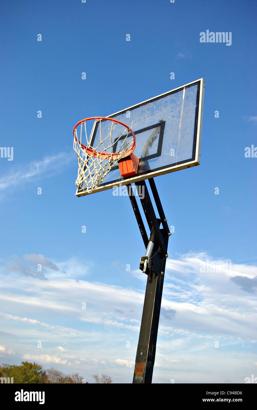 Un objectif de basket-ball avec le ciel pour un arrière-plan dans le pays. Photo Stock
