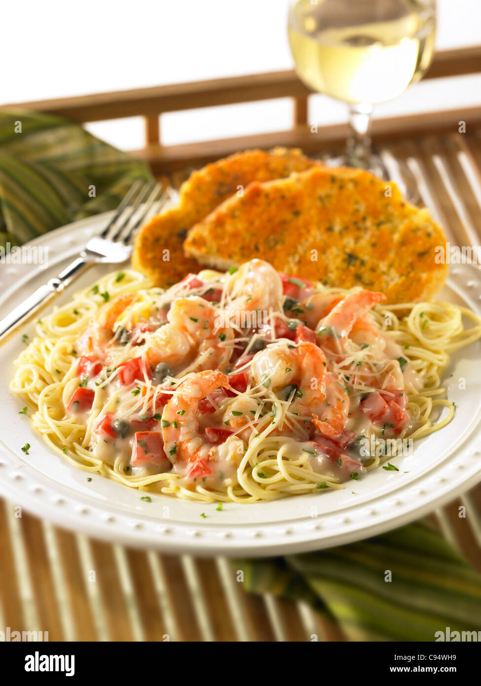 Repas de pâtes de crevettes dans une sauce crémeuse garnie de fromage Parmesan et servi avec du pain à l'ail et Banque D'Images