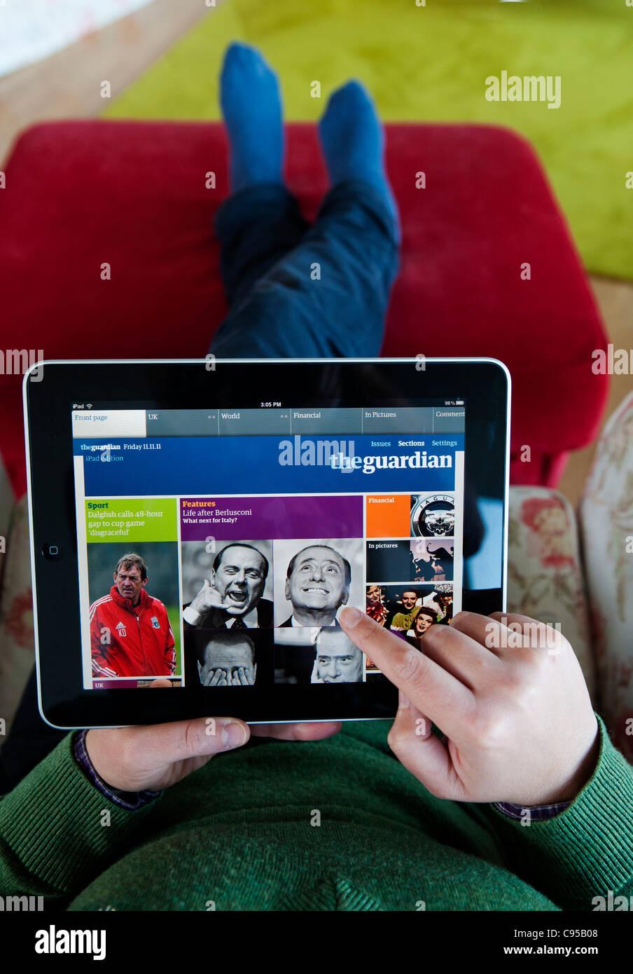 Femme à l'aide de l'ordinateur tablette iPad pour lire le journal The Guardian, édition en ligne Photo Stock