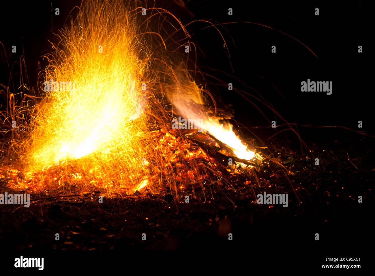 Feu avec flammes et étincelles. Orange intense, jaune de feu contre un fond noir nuit. Photo Stock
