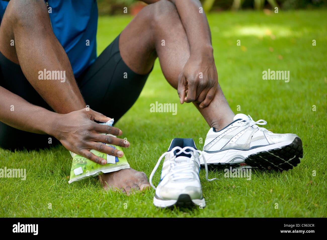 L'homme d'appliquer un sac de glace à sa cheville blessée. Photo Stock