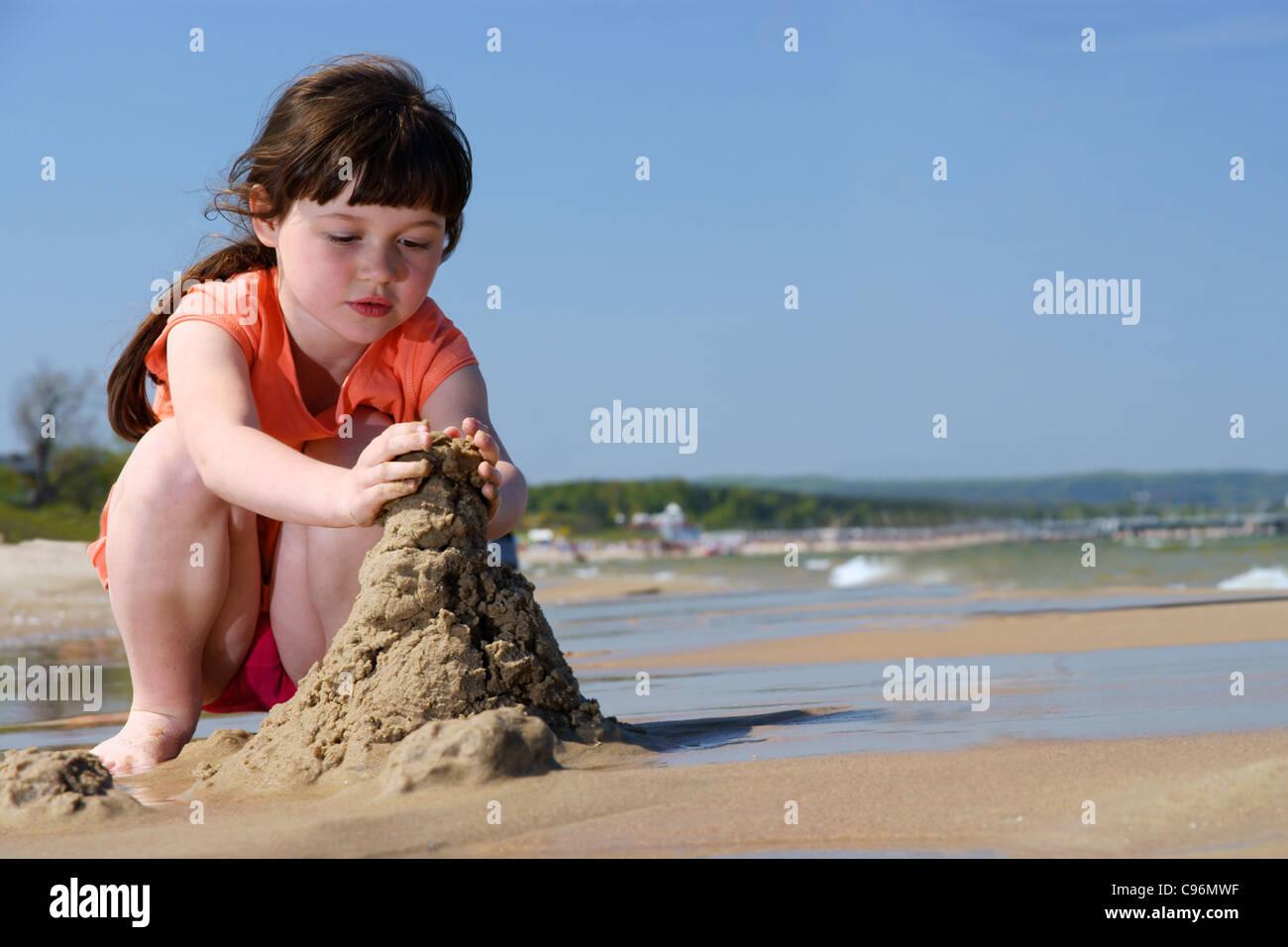 Les enfants sur la plage, jeune fille jouant dans le sable