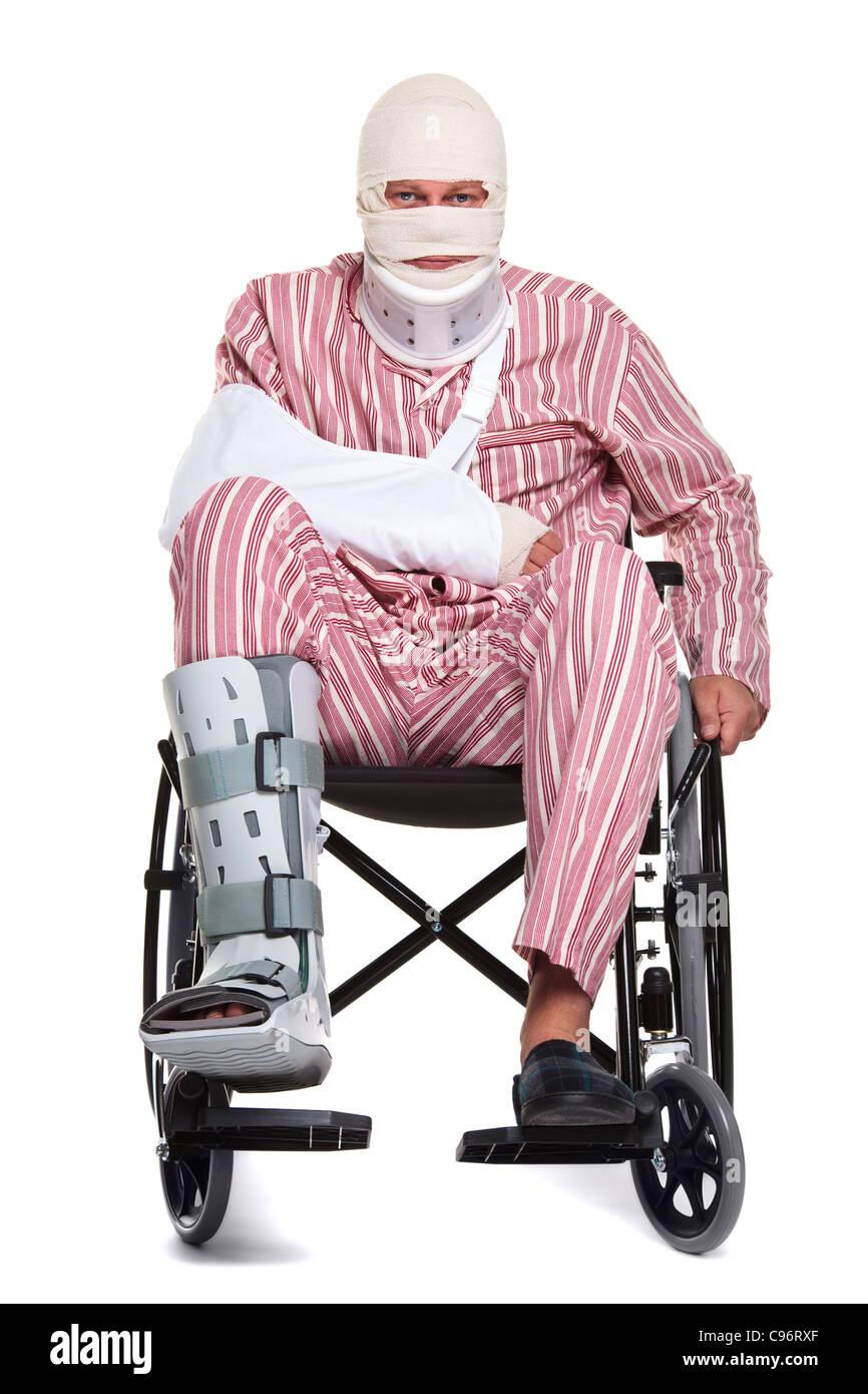 Photo d'un homme avec diverses blessures portant pyjames rayé et assis dans un fauteuil roulant. Photo Stock