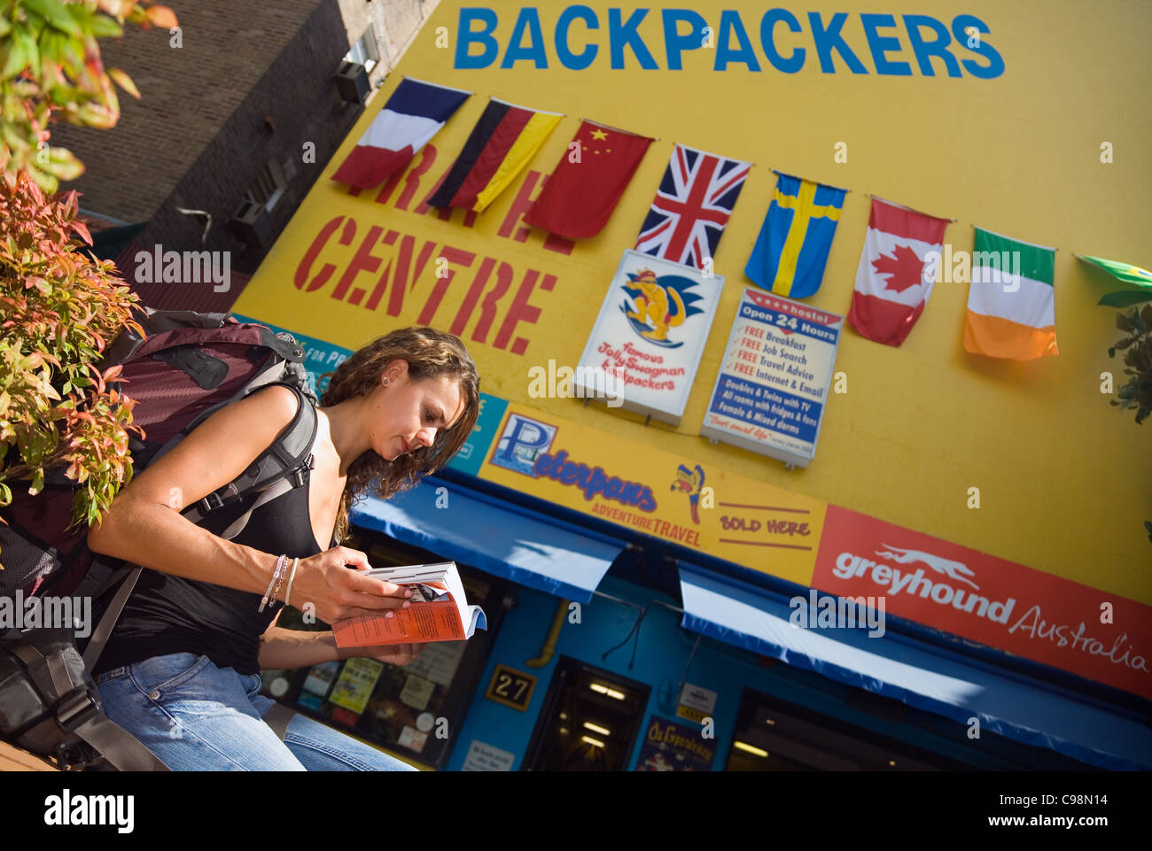 Young woman reading guidebook en dehors d'un backpacker hostel. Kings Cross, Sydney, New South Wales, Australia Photo Stock