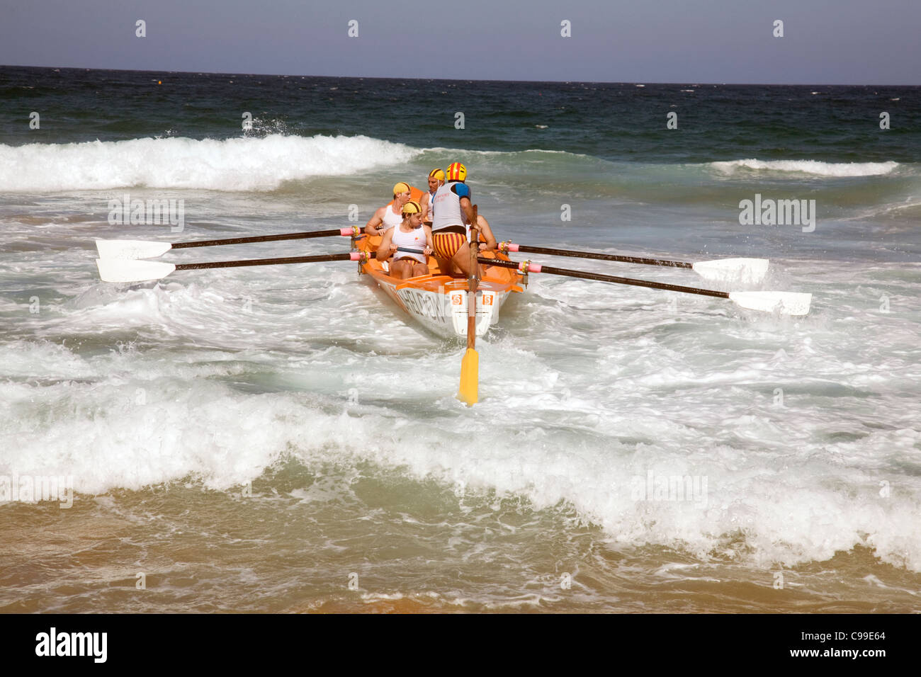 L'équipage d'un canot de sauvetage australien traditionnel surf voile aviron dans une course au large Photo Stock