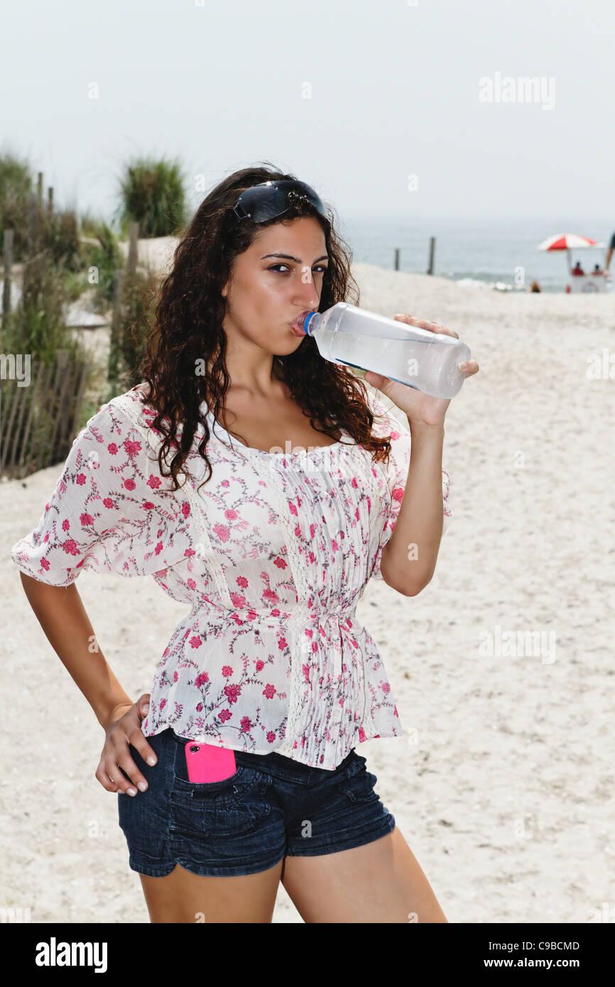 Jeune femme à boire de l'eau en bouteille sur la plage, Atlantic City, New Jersey Photo Stock