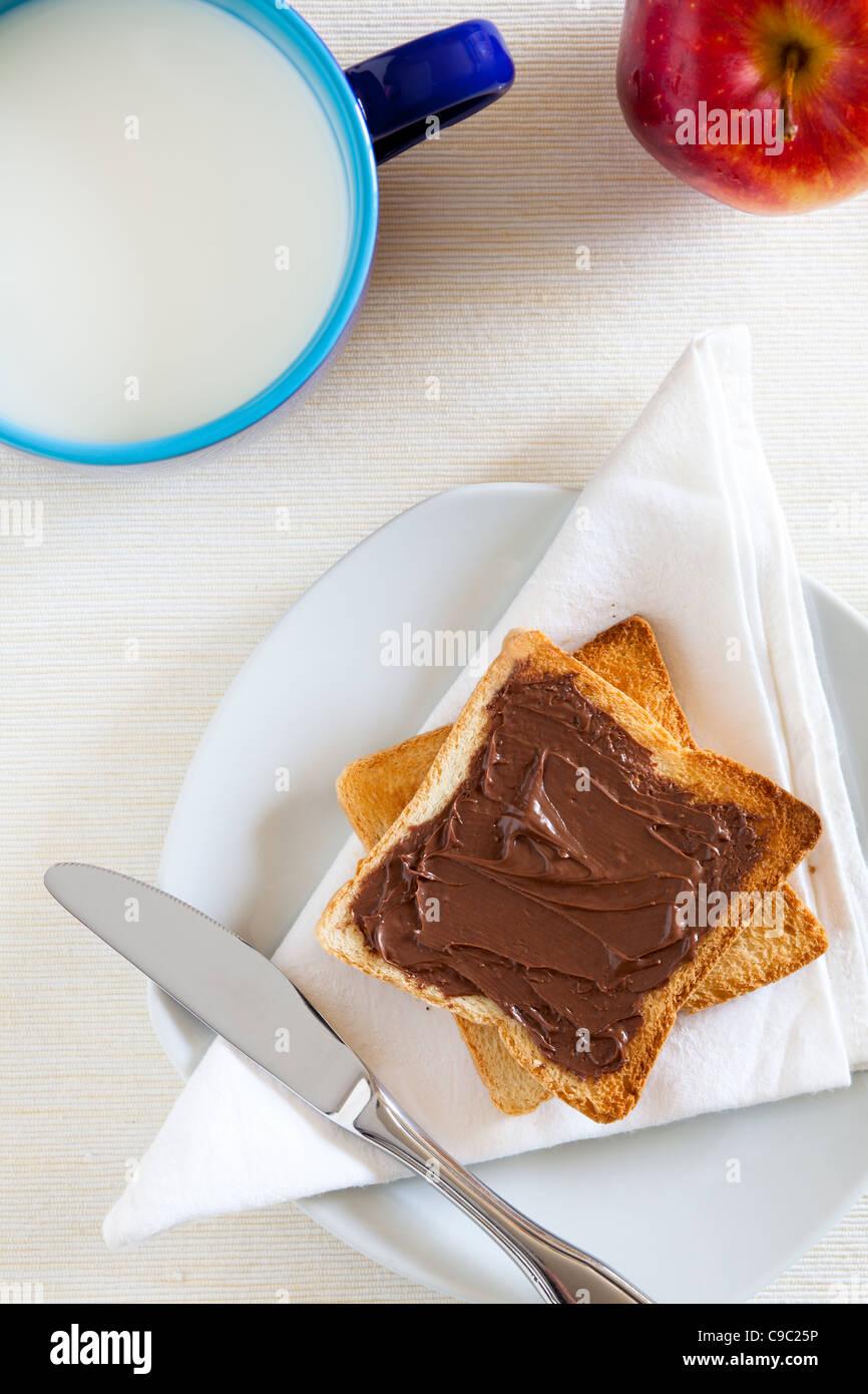 Petit déjeuner avec chocolat à tartiner sur des toasts et du lait Photo Stock