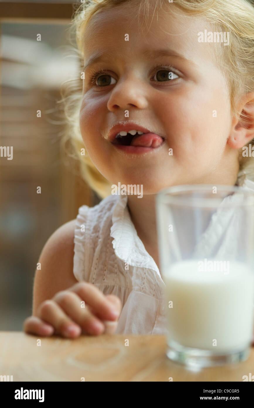 Petite fille profiter de verre de lait Banque D'Images
