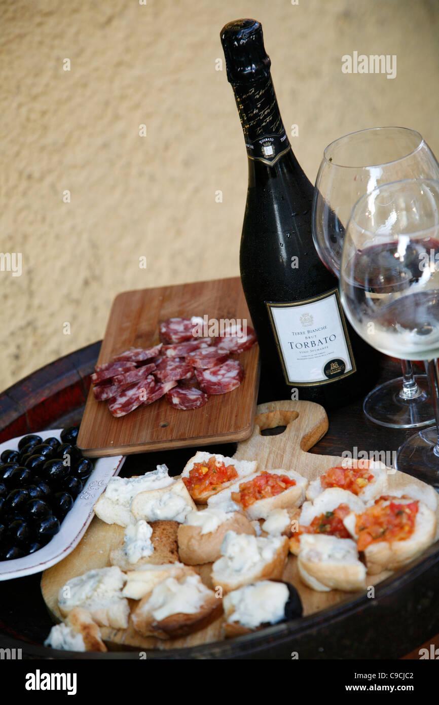 Assiette de fromage, salami, des olives et du vin à l'Osteria Da Lio, La Maddalena, en Sardaigne, Italie. Photo Stock