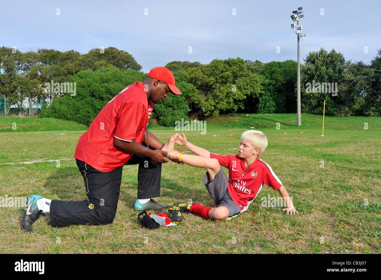 Entraîneur de football évalue la blessure d'un joueur de l'équipe jeunesse Cape Town Afrique Photo Stock