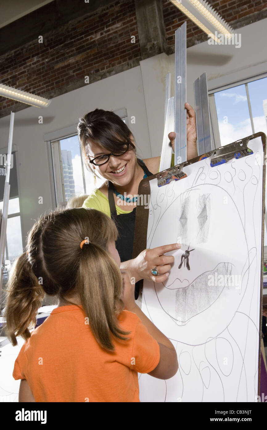 Un professeur d'art avec son étudiante s'appuyant sur chevalet dans la classe d'art Banque D'Images