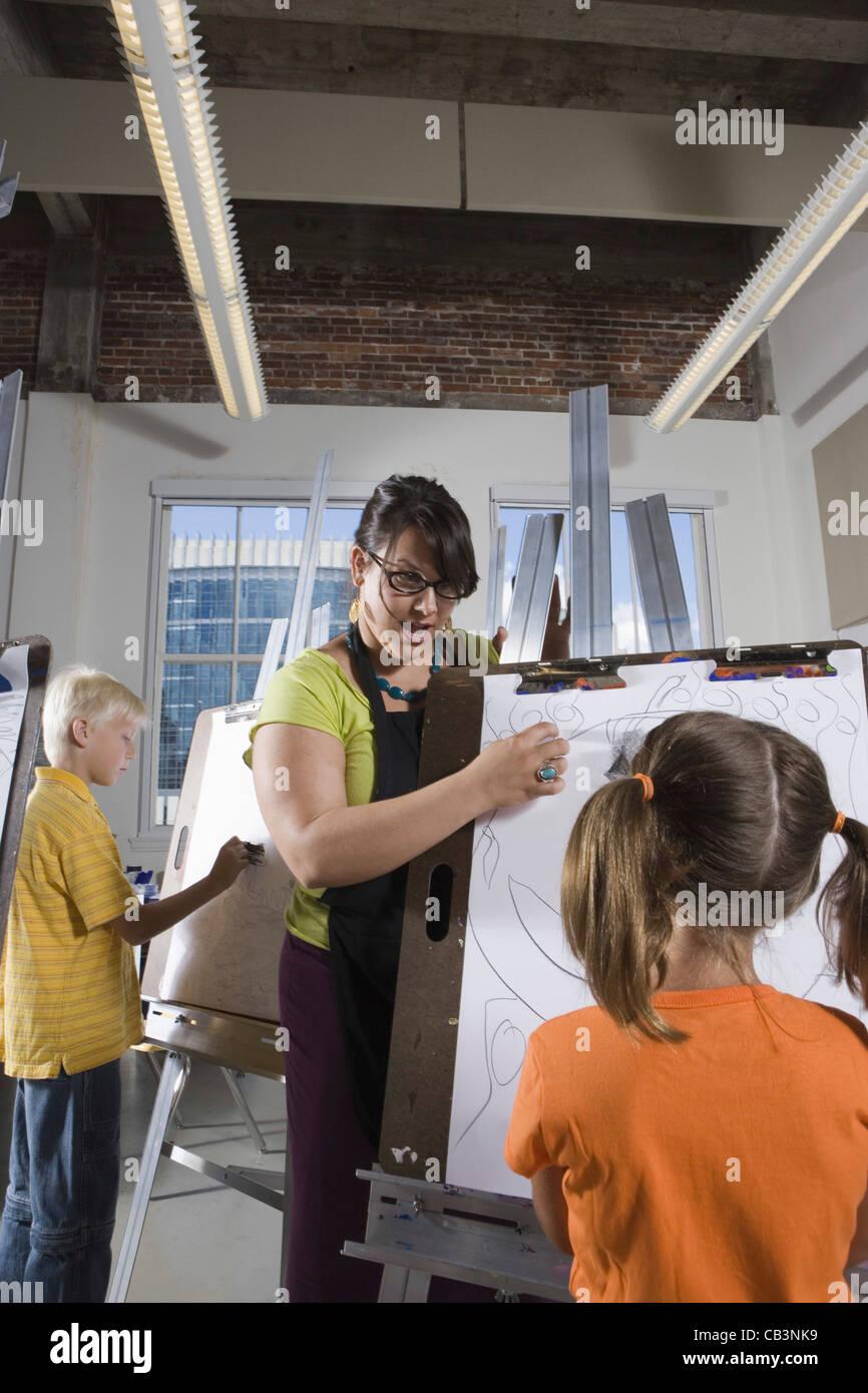 Un professeur d'art avec son étudiante dimensions sur des chevalets dans la classe d'art Banque D'Images