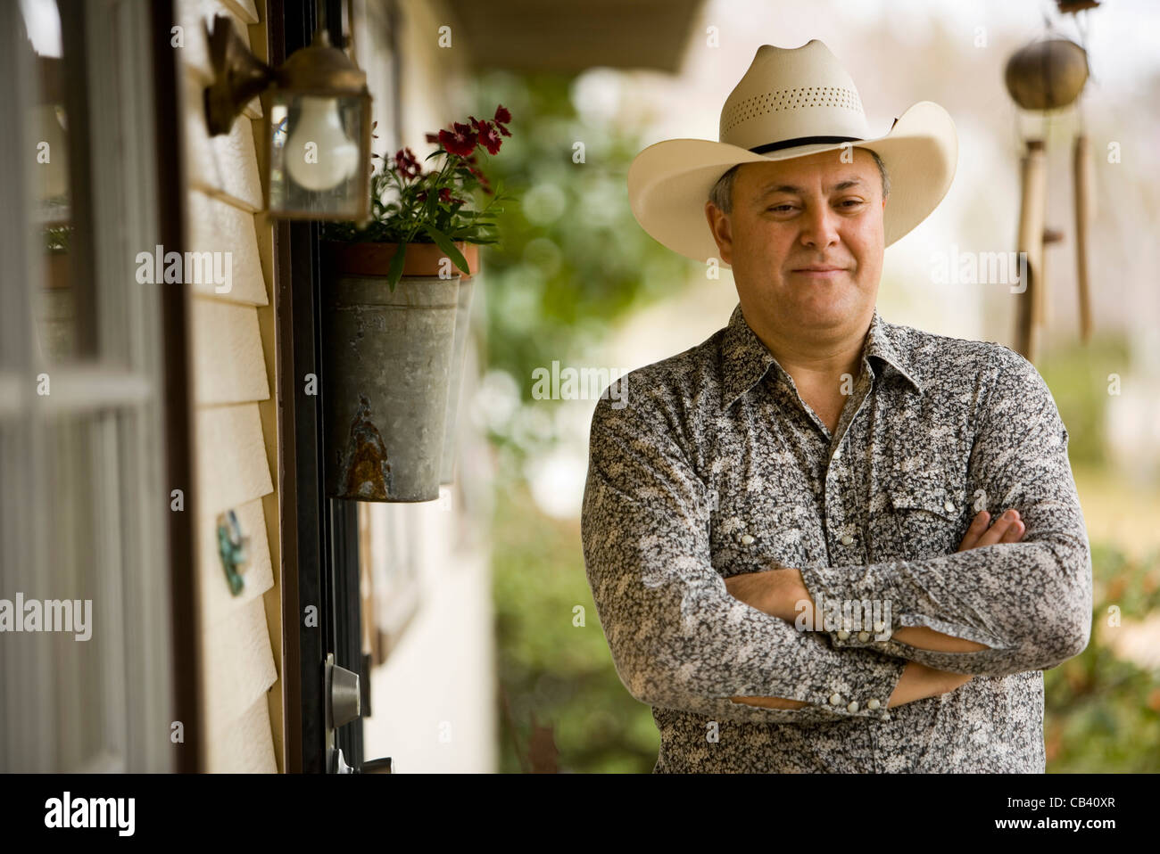 Vue d une maturité contemplative man wearing cowboy hat in front of house  Photo Stock a50e69d8a2cb