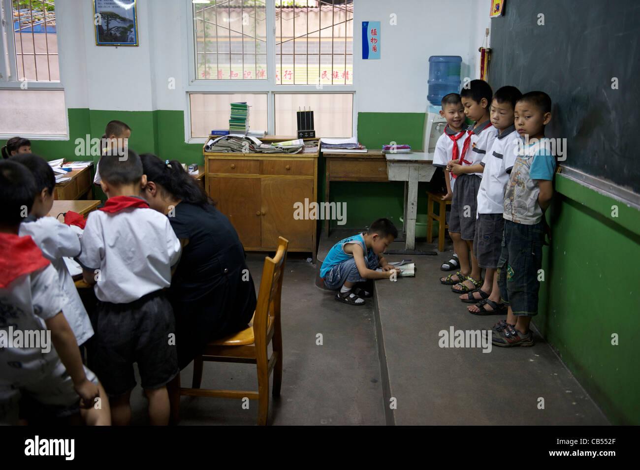 Enseignant fait 4 élèves sont devant le tableau noir dans la classe comme une punition dans une école Photo Stock