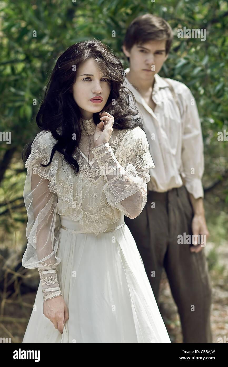 Une jeune femme aux longs cheveux noirs s'éloignent d'un jeune homme habillé en costume Photo Stock