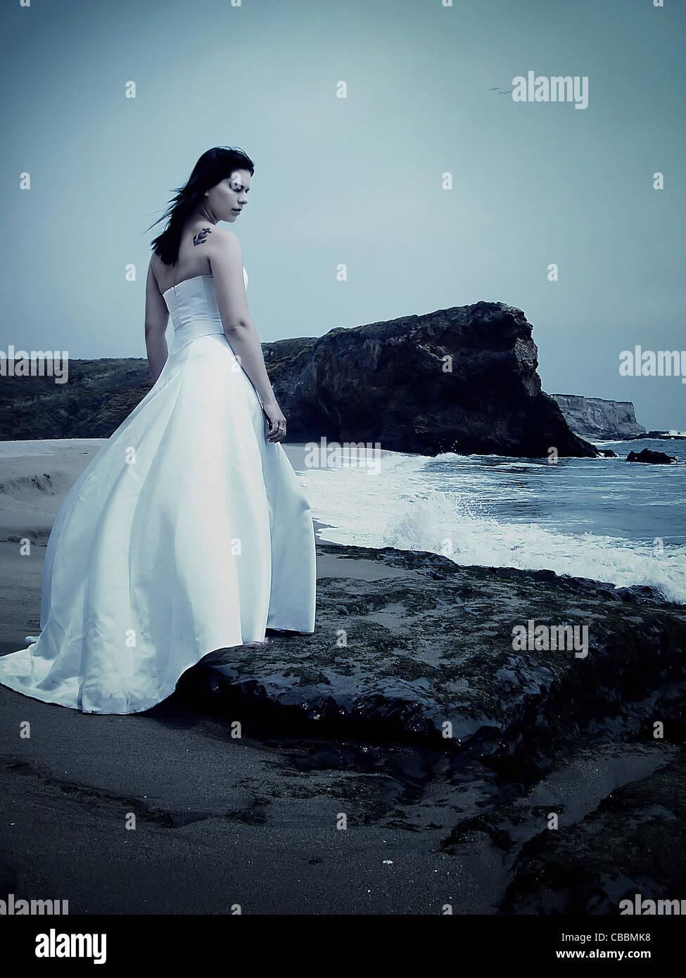 Une femme portant une robe de mariage sur une plage seul avec ressac Photo Stock