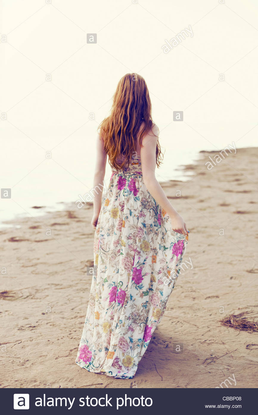 Jeune femme en robe longue marche sur la plage Photo Stock