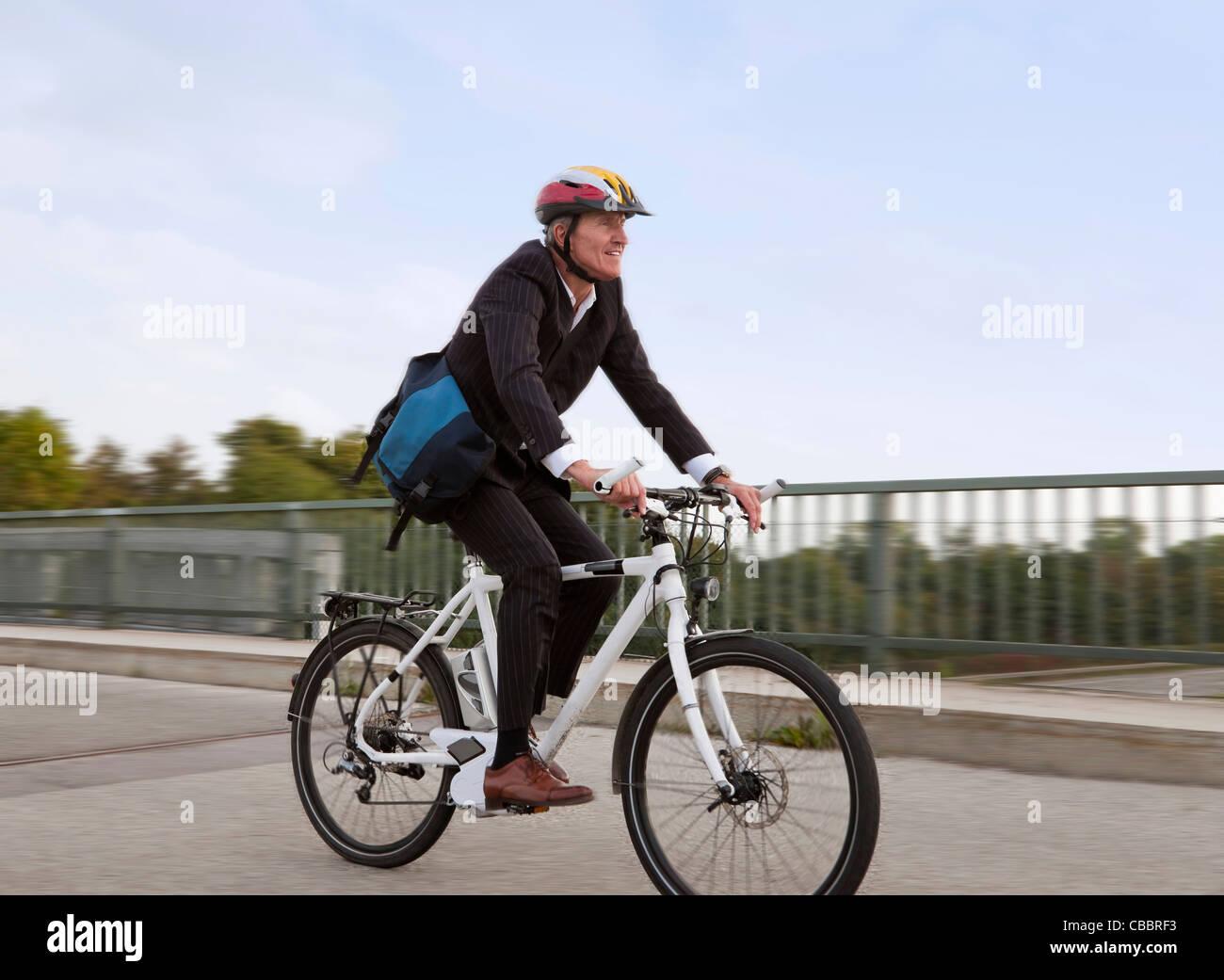 Businessman riding bicycle on bridge Banque D'Images