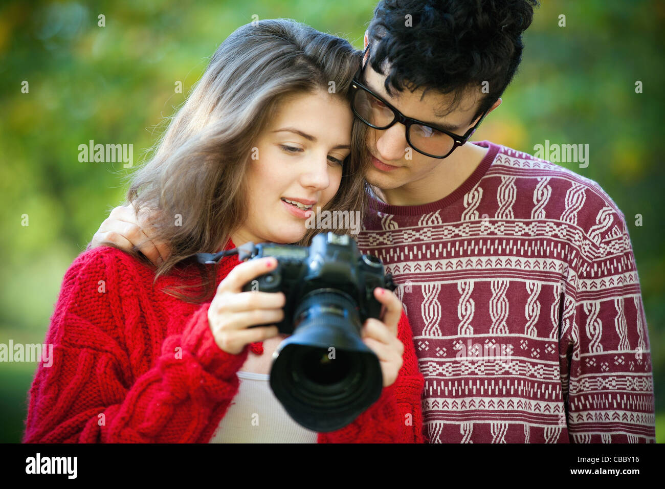 Teenage girl using camera with boyfriend Banque D'Images