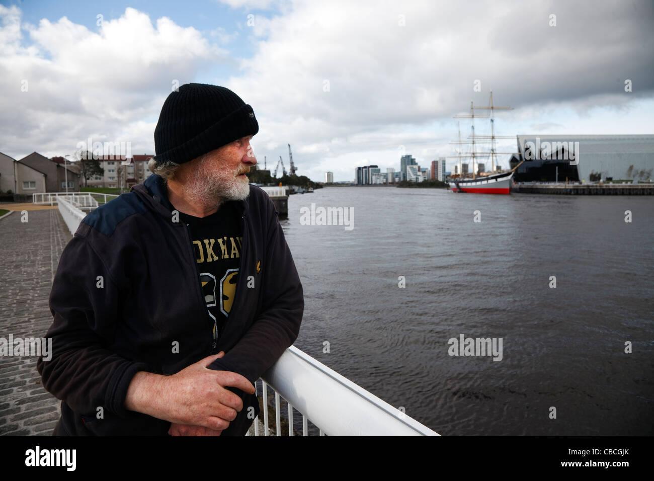 Homme adulte au chômage à la recherche sur les rails d'un chemin de ronde à Govan, de l'autre Photo Stock