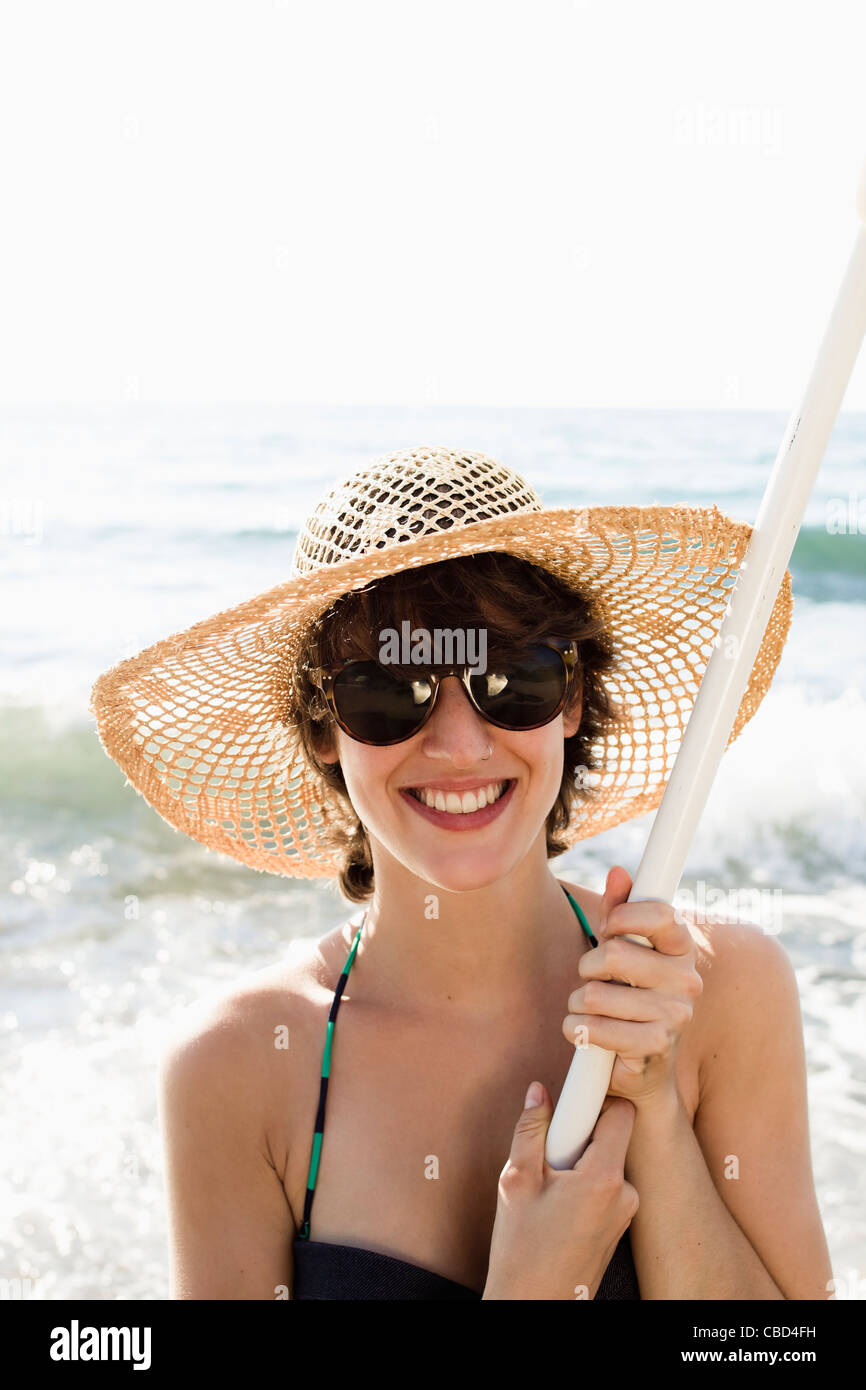 Woman holding pole on beach Photo Stock