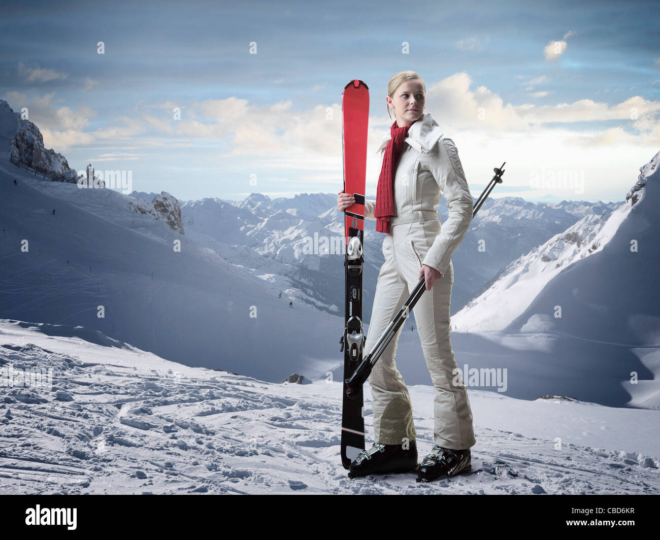Woman carrying skis on snowy slope Photo Stock