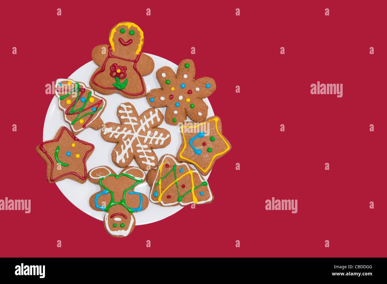 Gingerbread cookies colorés sur une plaque blanche à l'arrière-plan rouge Banque D'Images