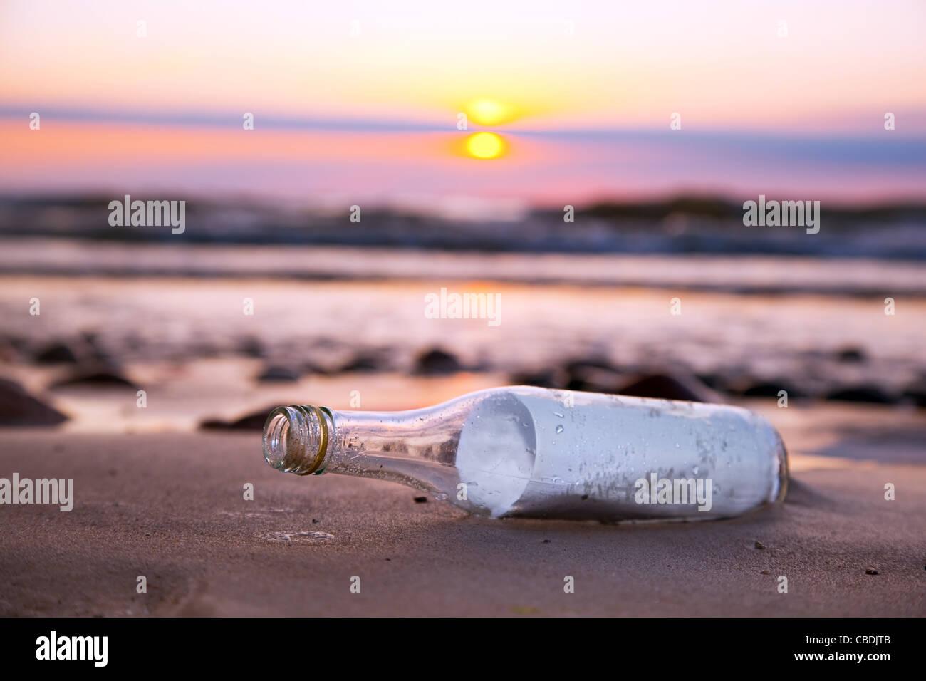 Message dans une bouteille à la mer sur la plage au coucher du soleil Photo Stock