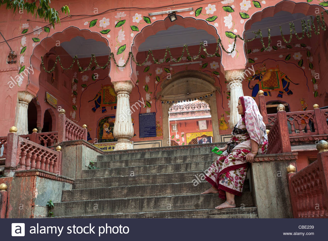 Une dame se repose devant un temple à l'ancienne ville de Jaipur, Rajasthan, Inde Photo Stock