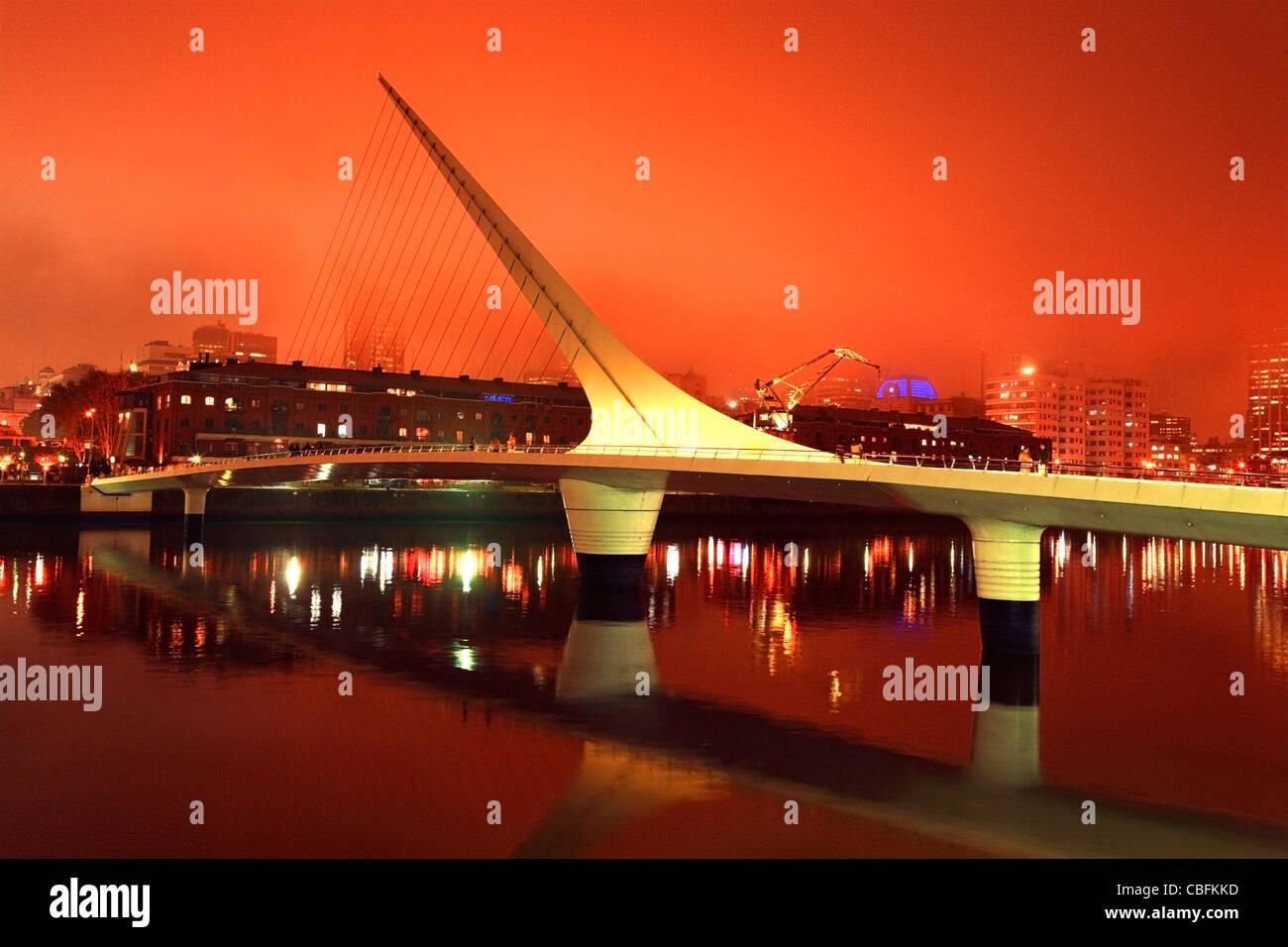 Pont de la Femme vue au coucher du soleil orange orageux, avec silhouette ville au fond. Photo Stock