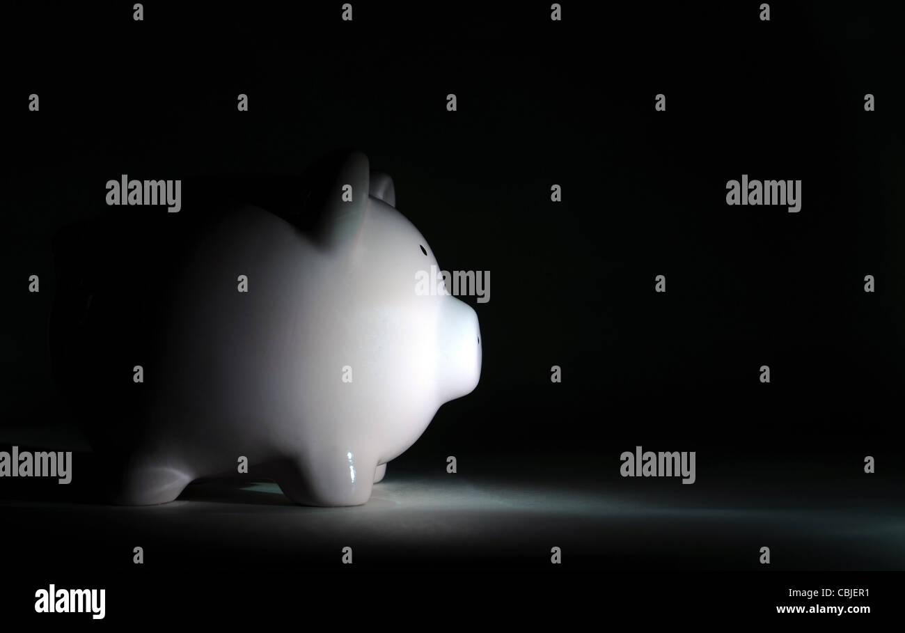 Tirelire en lumière sombre morosité économique NOUVEAU RALENTISSEMENT RÉCESSION FINANCIÈRE Photo Stock