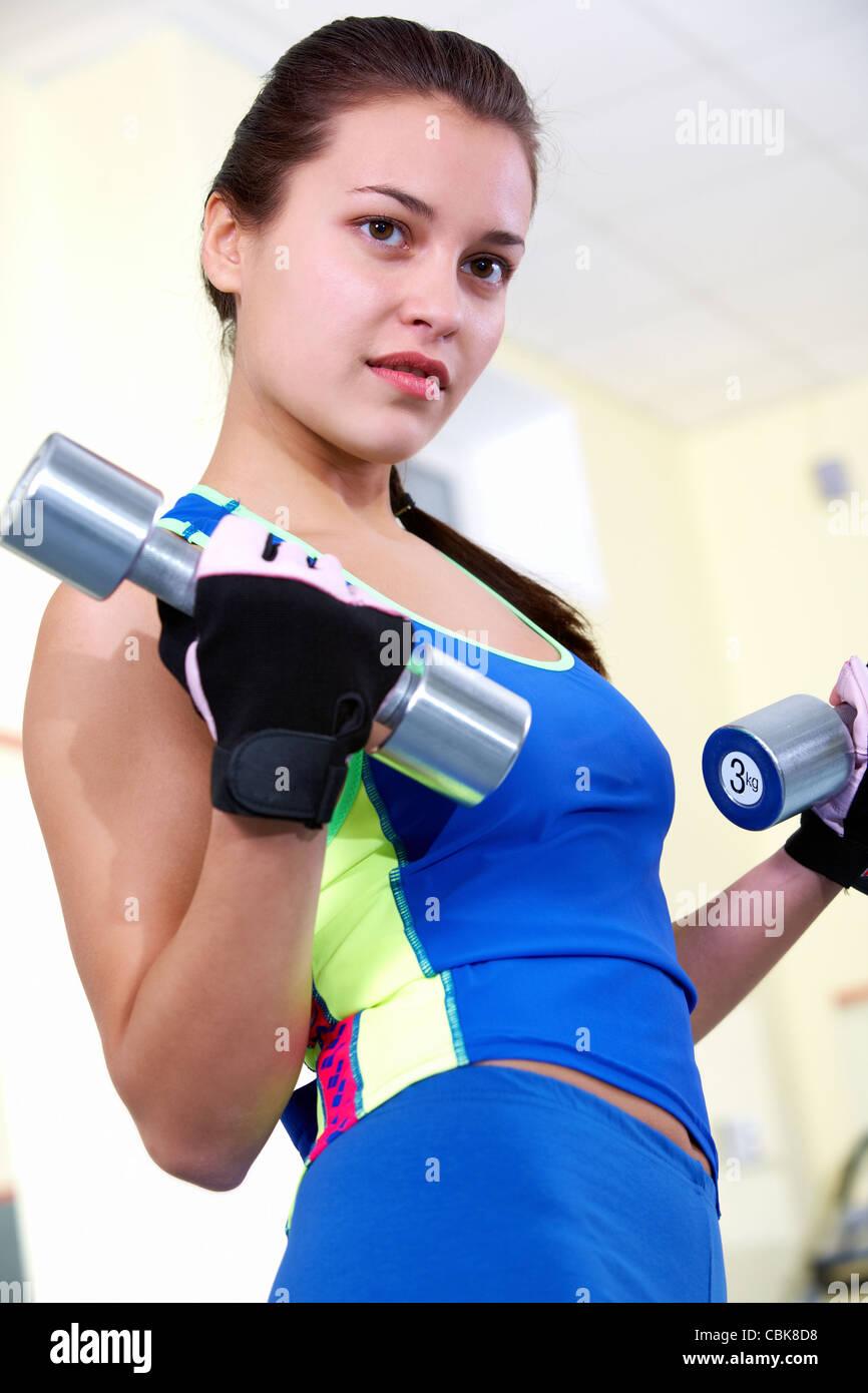 Portrait de jeune femme en faisant des exercices avec haltères fitness Photo Stock