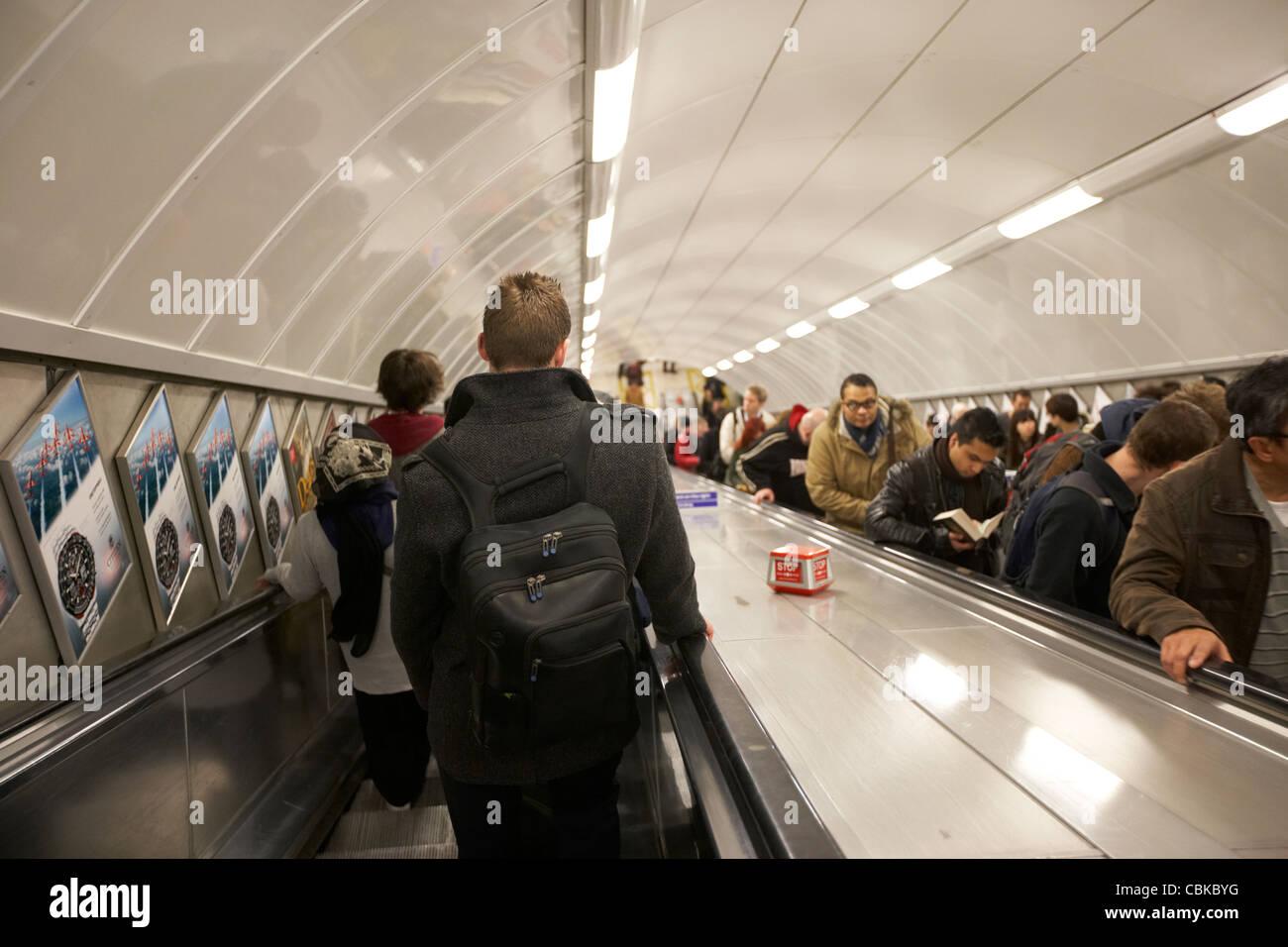 Les passagers et les usagers sur l'escalier mécanique à la station de métro de Londres Angleterre Photo Stock