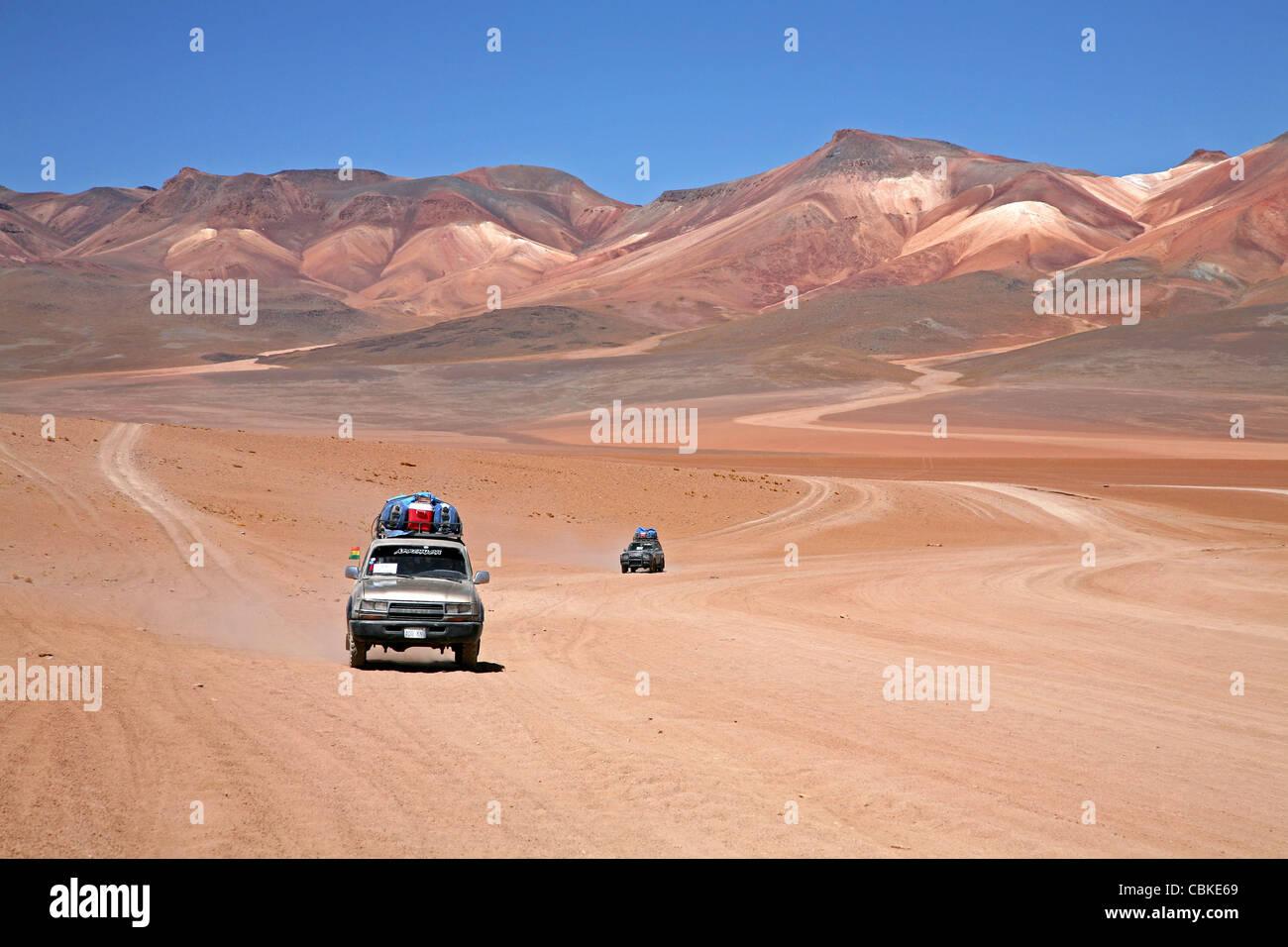 Les véhicules à quatre roues motrices de la conduite sur piste de terre sur l'Altiplano en Bolivie Photo Stock