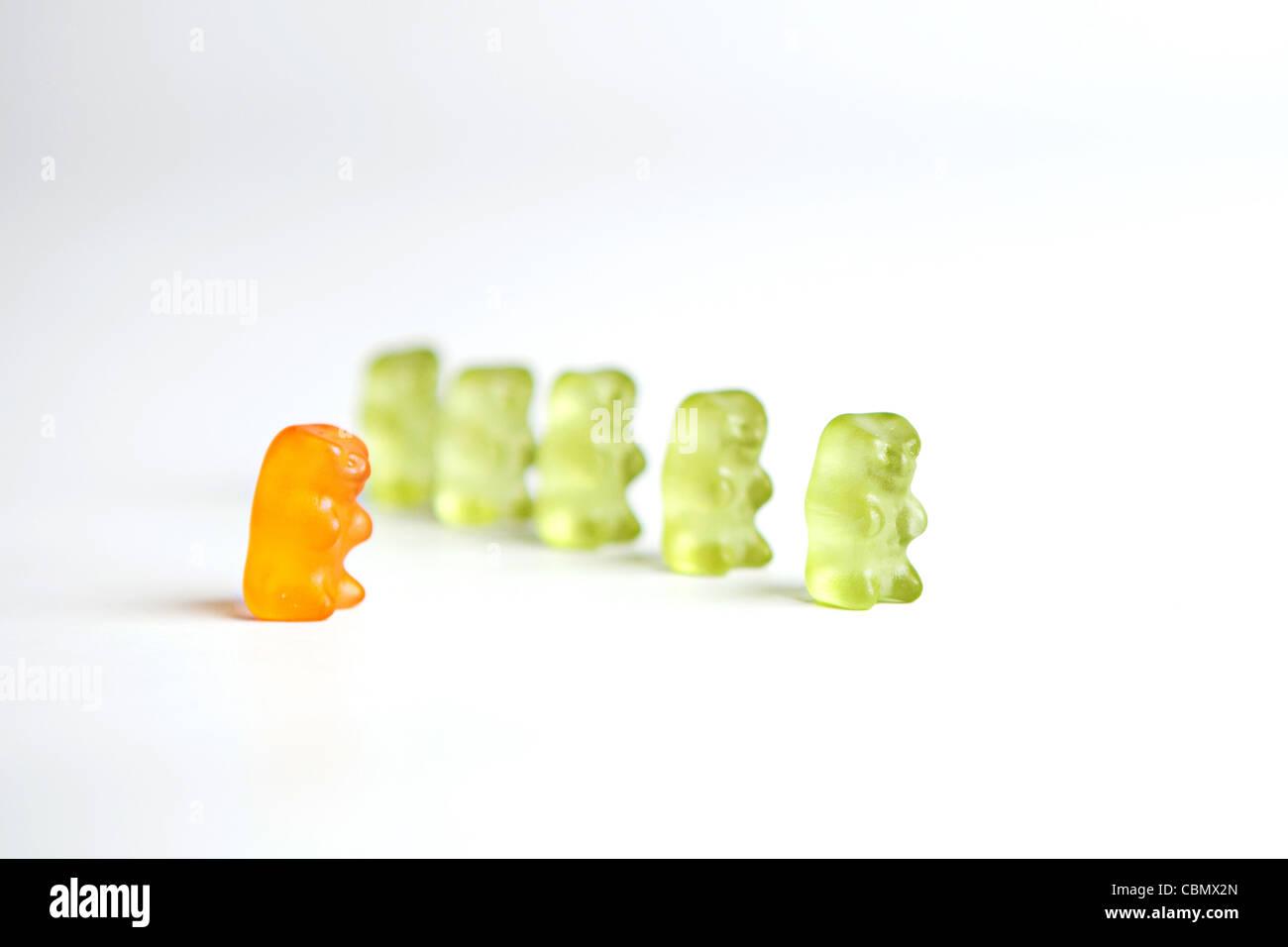 Une ligne d'un livre vert ours gommeux avec un 'odd one out' ours orange Photo Stock
