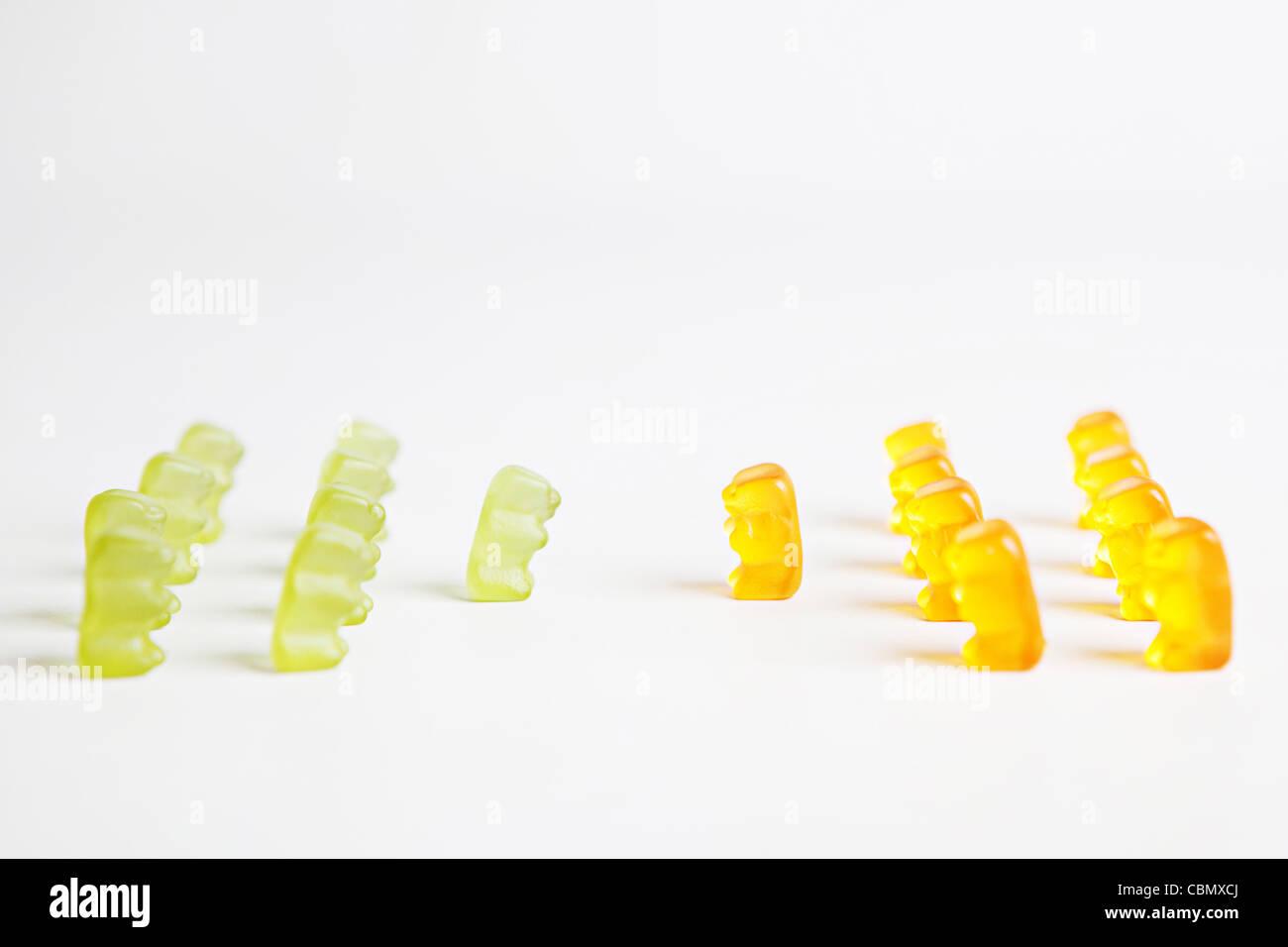 Deux rangées de vert et orange ours gommeux en face de l'autre, de donner un message conceptuel sur le leadership Banque D'Images