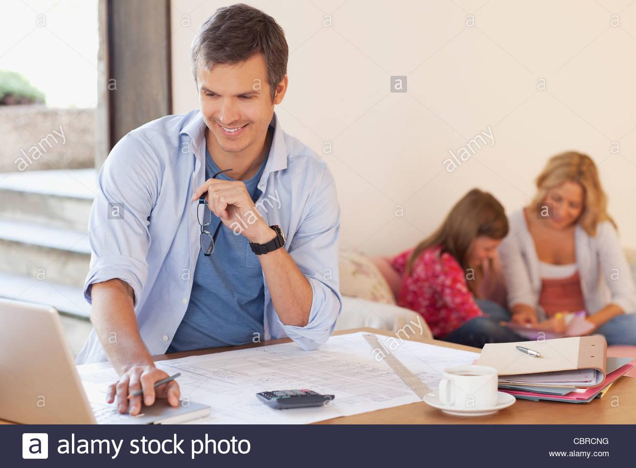 L'homme travaillant avec la famille en arrière-plan Photo Stock