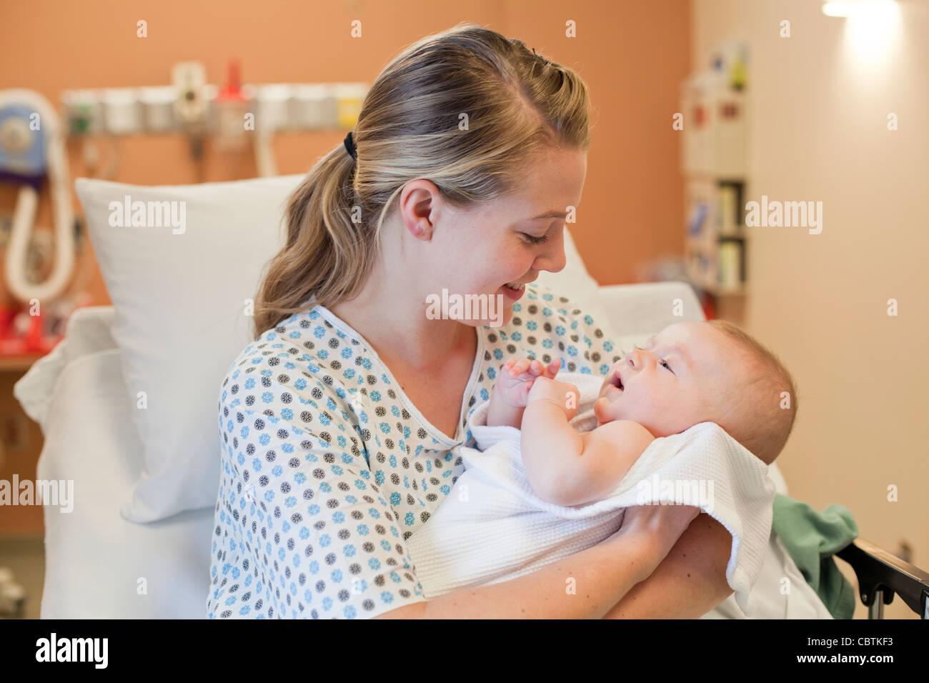 Jeune mère tenant son nouveau-né à l'hôpital. Photo Stock