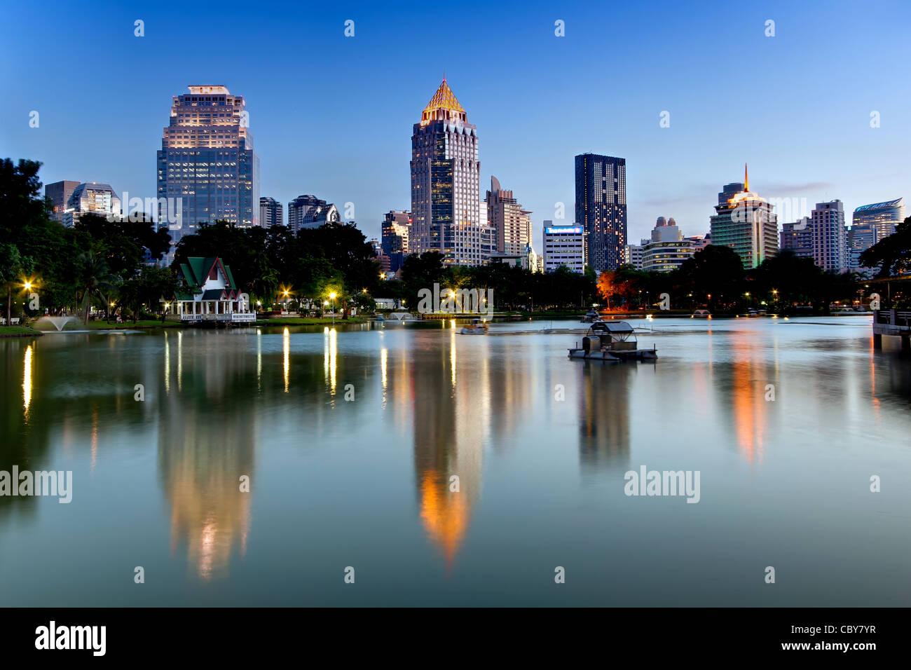 Vue vers Silom et Rama IV Road de parc Lumpini au crépuscule, Bangkok. Photo Stock