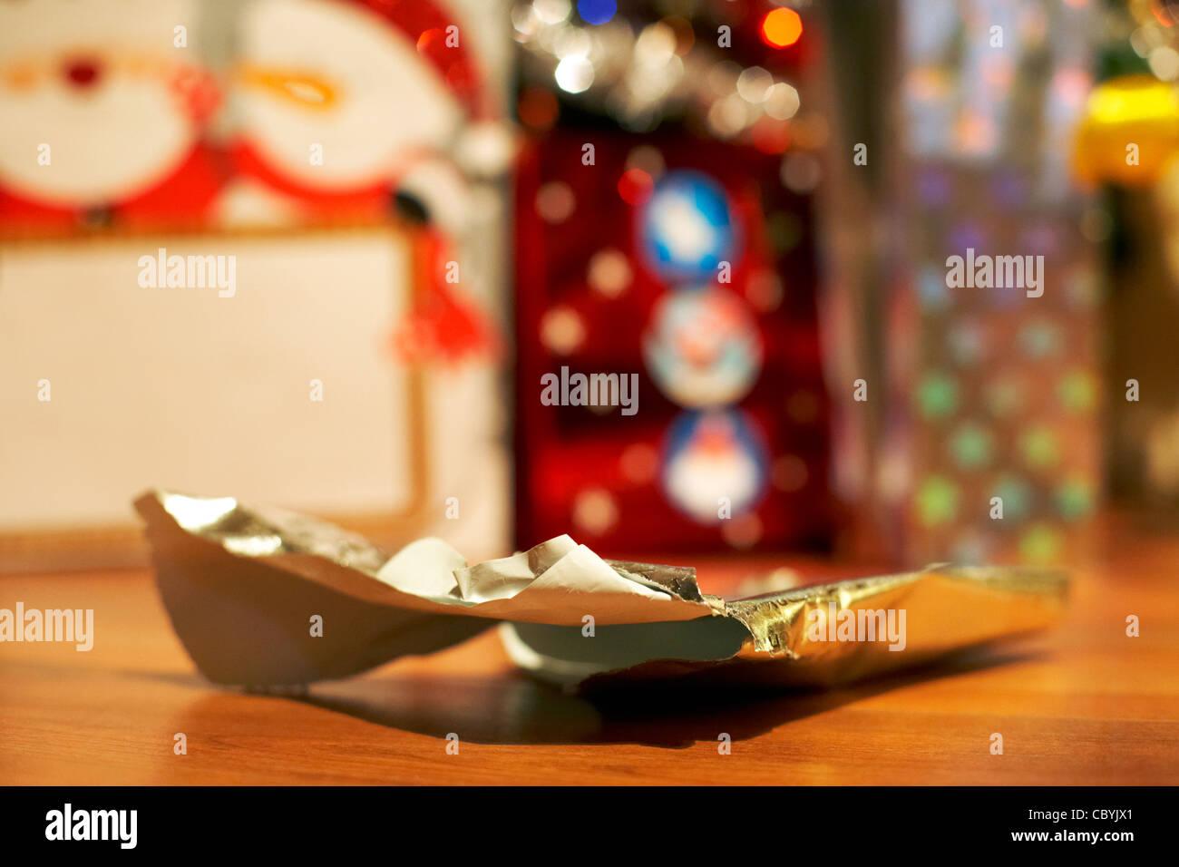Papier d'emballage de Noël allongé sur le sol après l'ouverture présente Photo Stock