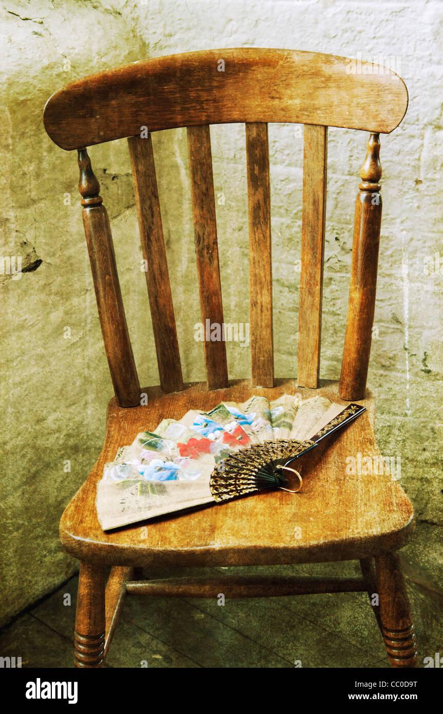 Ventilateur à l'ancienne sur une vieille chaise en bois Photo Stock