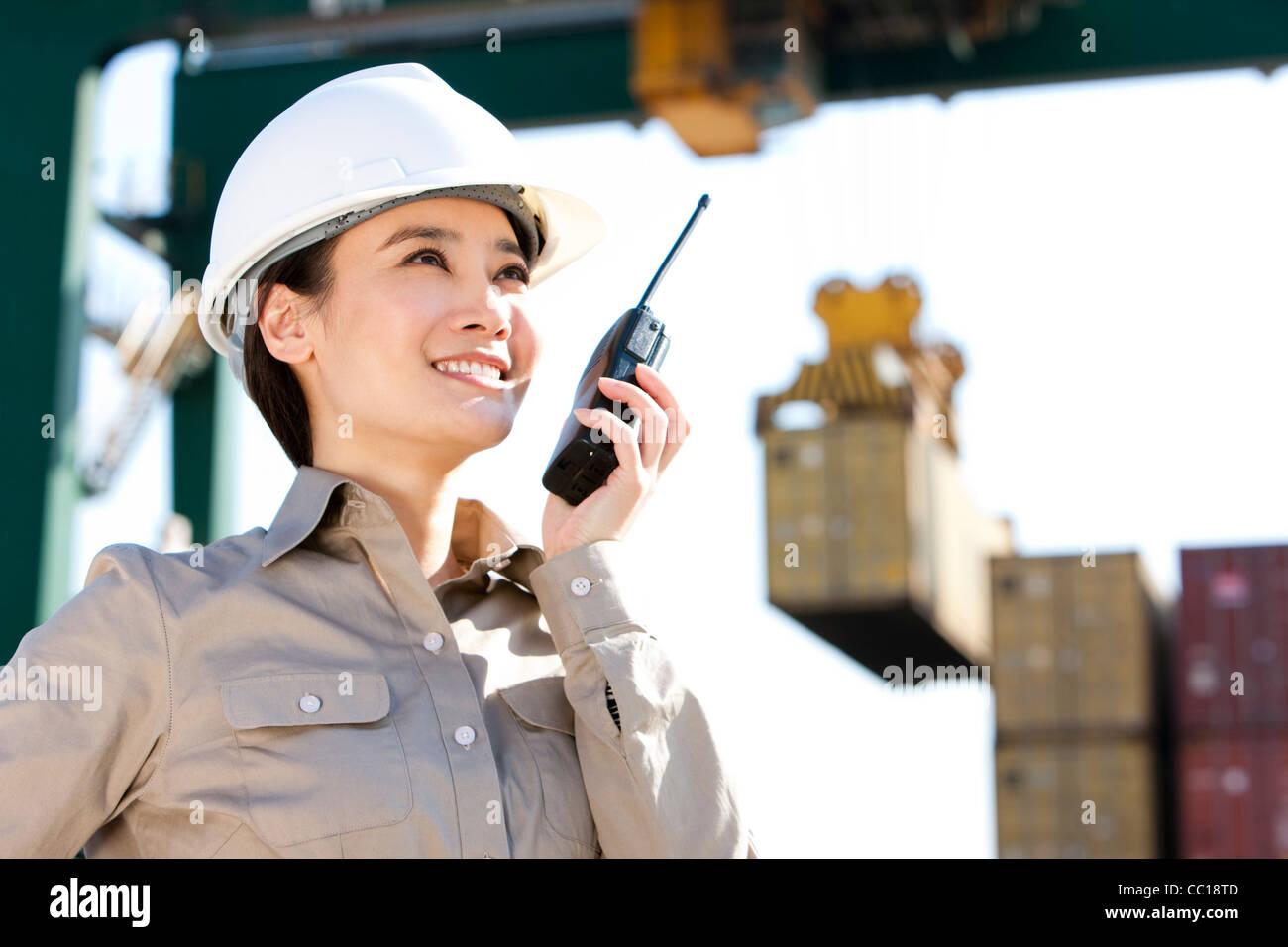 Travailleur de l'industrie d'expédition de diriger avec ses grues talkie-walkie Photo Stock