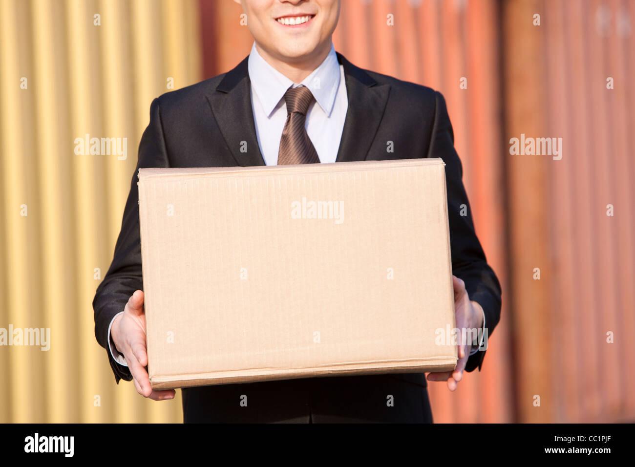 Businessman carrying une boîte en carton avec les conteneurs de fret à l'arrière-plan Photo Stock