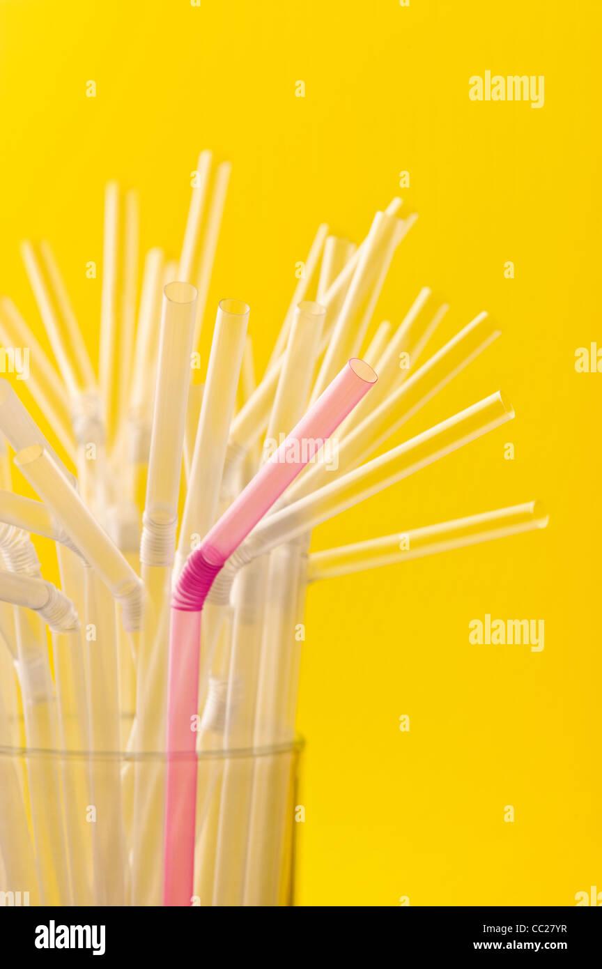 Une paille rose parmi un groupe de pailles claires Photo Stock